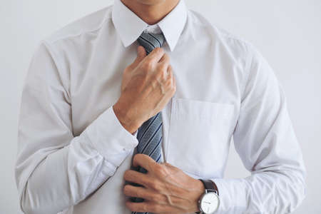 Close up of Young attractive businessman wears a gray tie and adjusting tie.