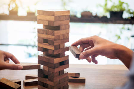 Images of hand of businesspeople placing and pulling wood block on the tower, Alternative risk concept, plan and strategy in business, Risk To Make Business Growth Concept With Wooden Blocks. Standard-Bild