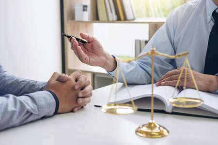 Richterhammer mit Waage der Gerechtigkeit, Geschäftsleute und männliche Rechtsanwälte, die Vertragspapiere in der Kanzlei im Amt besprechen Konzepte des Gesetzes.