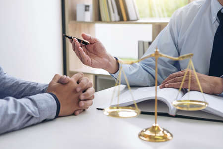 Sędzia młotek ze skalą sprawiedliwości, biznesmeni i prawnicy omawiający dokumenty kontraktowe w kancelarii prawnej. Pojęcia prawa.