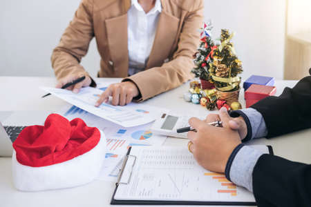 Merry Christmas and Happy New Year, Young business team are celebrating holiday in workplace are sitting in Santa hats,they are thinking travel trip with family, Working in the last month of year. Stock Photo