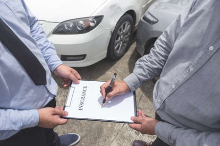 Insurance Agent examine Damaged Car and customer filing signature on Report Claim Form process after accident, Traffic Accident and insurance concept.