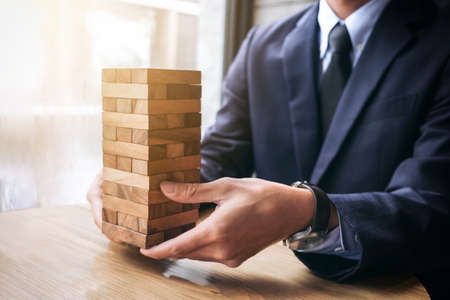 Alternatief risicoconcept, plan en strategie in zaken, jonge intelligente zakenman heft het houten spel, handen van uitvoerend duurzaam houtblok op de toren, Samenwerkingsbeheer op.