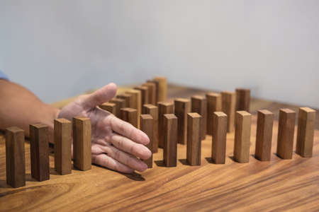 Risk and strategy in business, Close up of businessman hand stopping wooden block between three way from falling in the line of domino. Archivio Fotografico
