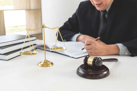 Close up of gavel, Male lawyer or judge working with Law books, report the case on table in modern office, Law and justice concept.