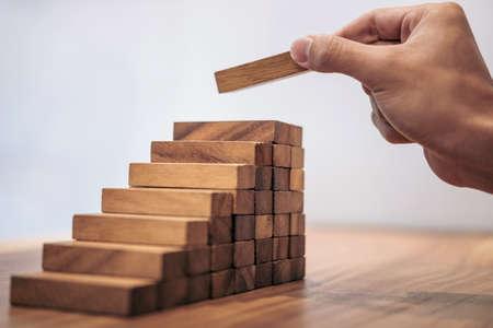 Alternatives Risikokonzept, Plan und Strategie im Geschäft, Risiko, Geschäfts-Wachstums-Konzept mit Holzklötzen zu machen, hat Hand des Mannes einen hölzernen Block aufstapeln und stapeln.