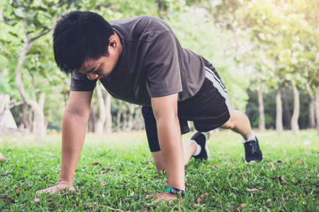 Man push-up exercise workout fitness doing outside on grass  in summer park. Stock Photo