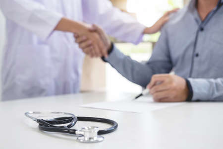 Doctor and patient shaking hands after treatment.
