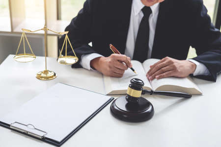 Judge gavel with Justice lawyers, Businessman in suit or lawyer working on a documents. Legal law, advice and justice concept. Stock Photo