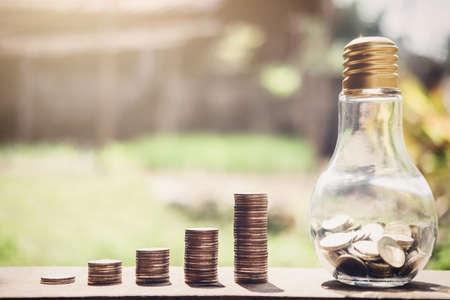 Apilando monedas y dinero creciendo para ahorrar, Moneda en botella de vidrio con pila de dinero para la inversión en planificación de negocios. Foto de archivo - 93857664