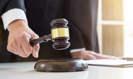 Close up of Male lawyer or judge hands striking the gavel on sounding block, working with Law books, report the case on table in modern office, Law and justice concept. Stock Photo