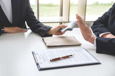 Bribery and corruption concept, senior businessman manager refusing receive money in the envelope to agreement contract, A bribe in the form of dollar bills. Stock Photo