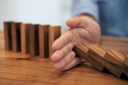 Risk and strategy in business, Close up of businessman hand stopping wooden block from falling in the line of domino.