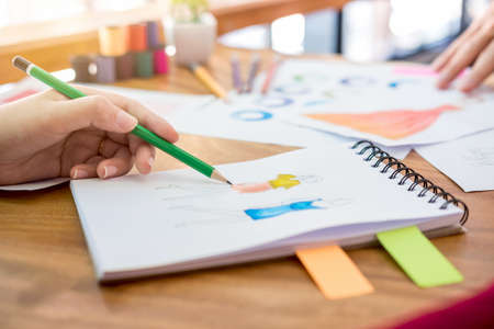 Close up of professional Fashion designer working and drawing sketches for clothes in workplace and color charts.