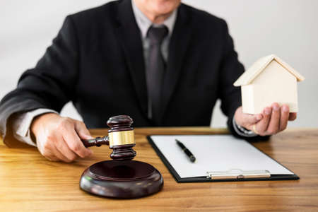 Male lawyer or judge hands striking the gavel on sounding block, working at courtroom for decide home insurance, Law and justice concept, Settle a house dealing lawsuit.