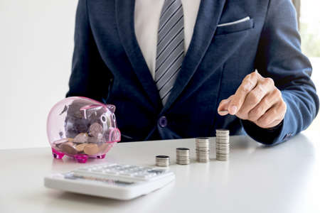 Businessman using calculator to analysis business investment and stacking coins arranged at office desk and piggy bank in modern office, financial concept.