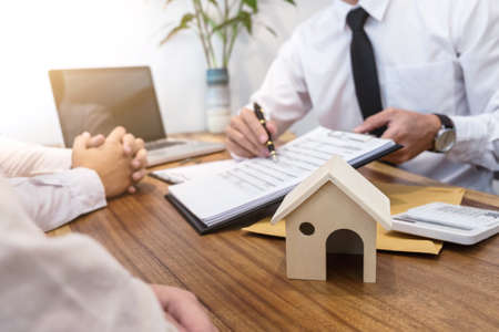 Business Signing a Contract Buy - sell house, insurance agent analyzing about home investment loan Real Estate concept.