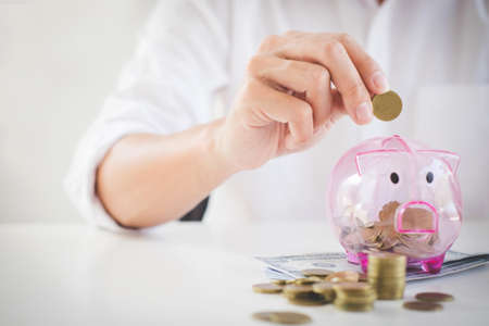 Businessman putting coins into piggy bank and using calculator to analysis business investment strategy with income of money coin and dollar, financial concept. Stock Photo