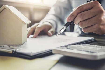 Zakenman of advocaat accountant werken financiële investeringen op kantoor, met behulp van calculator analyse financiën document rapport onroerend goed en woningkredietverzekering. Stockfoto
