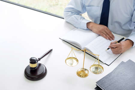 Judge gavel with scales of justice, male lawyers working having at law firm in office. Concepts of law. Stock Photo
