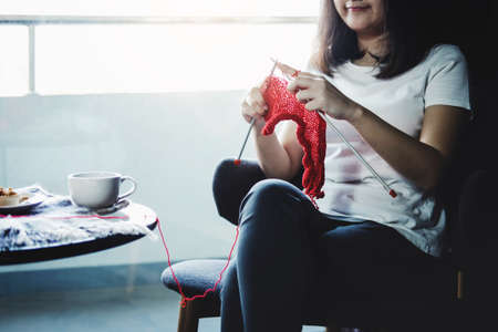 Close up shot of young woman hands knitting a red scarf handicraft in the living room on terrace at home. Stockfoto