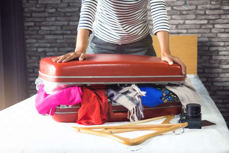 Travel and vacation concept, happiness young woman packing a lot of her clothes and stuff into suitcase on bed prepare for travel and journey trip in holiday. 스톡 콘텐츠 - 100680316