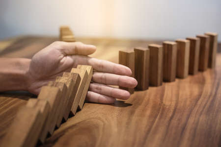 Risk and strategy in business, Close up of businessman hand stopping wooden block between two way from falling in the line of domino.