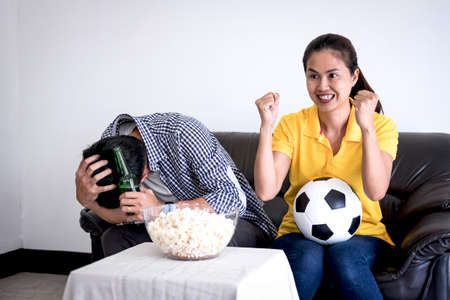 Young Asian couple love watching soccer match on tv and cheering football team, celebrating with beer and popcorn at home, sports and entertainment concept. Stockfoto
