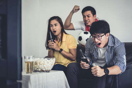 Group of friends fanclub watching soccer match on tv and cheering football team, celebrating with beer and popcorn at home, sports and entertainment concept.