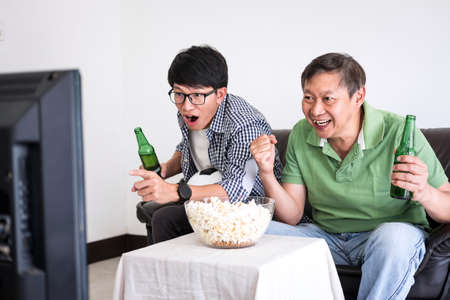 Young Asian Man and father watching soccer match on tv and cheering football team, celebrating with beer and popcorn at home, sports and entertainment concept.