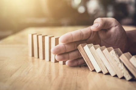 Strategy and successful intervention concept for business, businessman hand Stopping Falling wooden Dominoes effect from continuous toppled or risk. Stock Photo