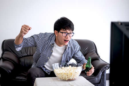 Young Asian Man fanclub watching soccer match on tv and cheering football team, celebrating with beer and popcorn at home, sports and entertainment concept.