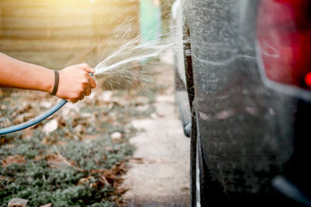 Man washing and cleaning car with spraying pressured water.