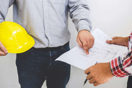 Architect or Engineer meeting working with partner on blueprint for architectural project in progress, construction and structure concept.