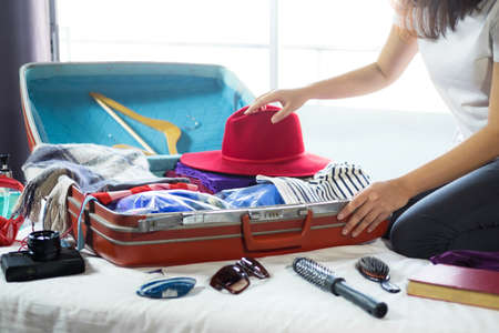 Travel and vacation concept, happiness young woman packing a lot of her clothes and stuff into suitcase on bed prepare for travel and journey trip in holiday. 免版税图像 - 104073407