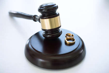 Close up of Judge gavel deciding on marriage divorce and two golden marriage ring. Reklamní fotografie