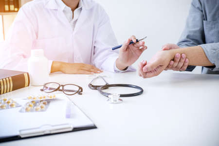 Doctor in white coat taking and checking the Patient's wrist pain during the examination. Stock Photo