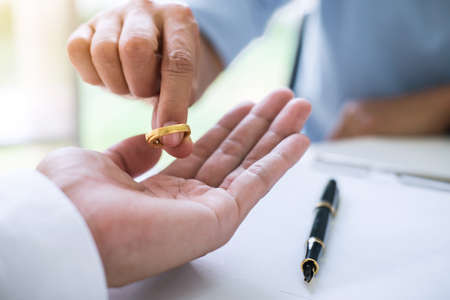 Husband and wife are signing decree of divorce (dissolution or cancellation) of marriage filing divorce papers and returning wedding ring. Stock fotó