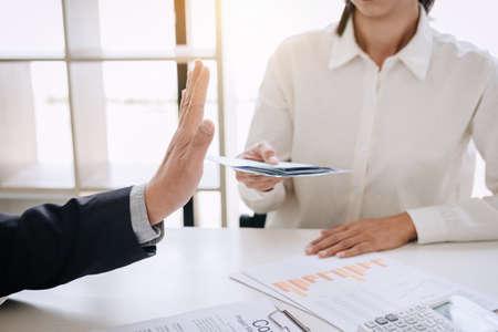 Concept de pot-de-vin et de corruption, chef d'entreprise senior refusant de recevoir de l'argent dans l'enveloppe pour conclure un contrat, un pot-de-vin sous forme de billets d'un dollar.