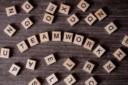 Concept presented by crossword with words teamwork with many wooden cubes on wooden background.