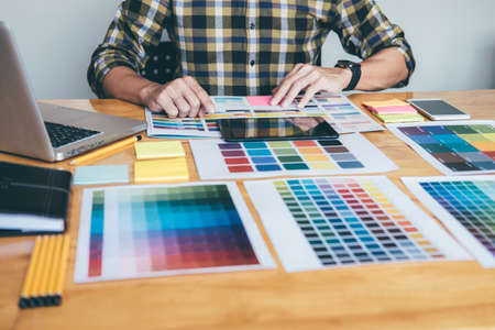 Young creative Graphic designer using graphics tablet to choosing Color swatch samples chart for selection coloring with work tools and accessories at workplace. 免版税图像