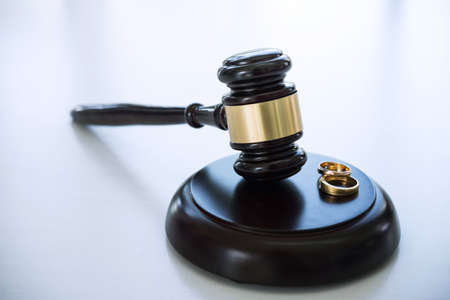 Close up of Judge gavel deciding on marriage divorce and two golden marriage ring. Stock fotó