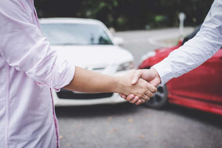 Insurance Agent and customer shaking hands after claim contact, Traffic Accident and insurance concept.