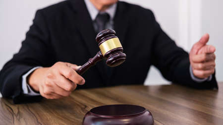 Male lawyer or judge hands striking the gavel on sounding block, working at courtroom, Law and justice concept.