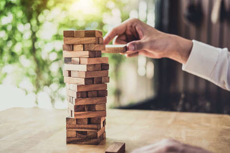 Images of hand of businesspeople placing and pulling wood block on the tower, Alternative risk concept, plan and strategy in business, Risk To Make Business Growth Concept With Wooden Blocks. Stock Photo
