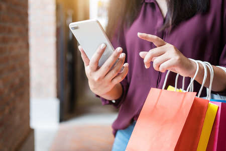 Consumerism, shopping, lifestyle concept, Young woman holding colorful shopping bags and smartphone enjoying in shopping. Imagens