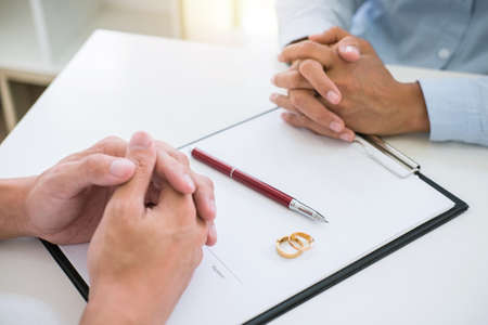 Husband and wife are reading divorce agreement and signing decree of divorce (dissolution or cancellation) of marriage filing divorce papers and two golden marry ring.