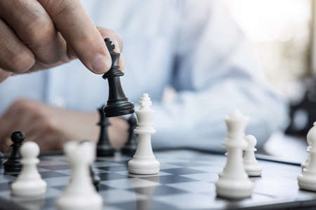 Businessman's hand playing chess game to development analysis new strategy plan, business strategy leader and teamwork concept for win and success.
