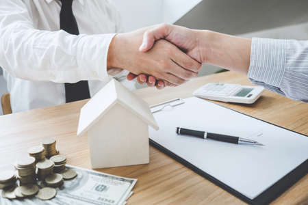 Agente di mediatore immobiliare e cliente si stringono la mano dopo aver firmato i documenti contrattuali per l'acquisto di immobili di proprietà, approvazione del mutuo ipotecario di concetto. Archivio Fotografico