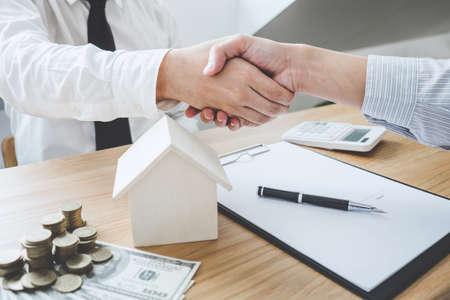 Makelaar in onroerend goed en klant die de hand schudden na ondertekening van contractdocumenten voor de aankoop van eigendomsrechten, goedkeuring van de hypotheeklening van het concept.